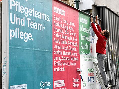 Caritas-Geschäftsführer Klaus Schwertner beim Kleben von Plakaten der Caritas zum Thema Pflege