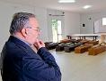 """Der italienische Kardinal Francesco Montenegro blickt auf die Särge ertrunkener Geflüchteter in der """"Casa della Fratenita"""" auf Lampedusa, Sizilien"""