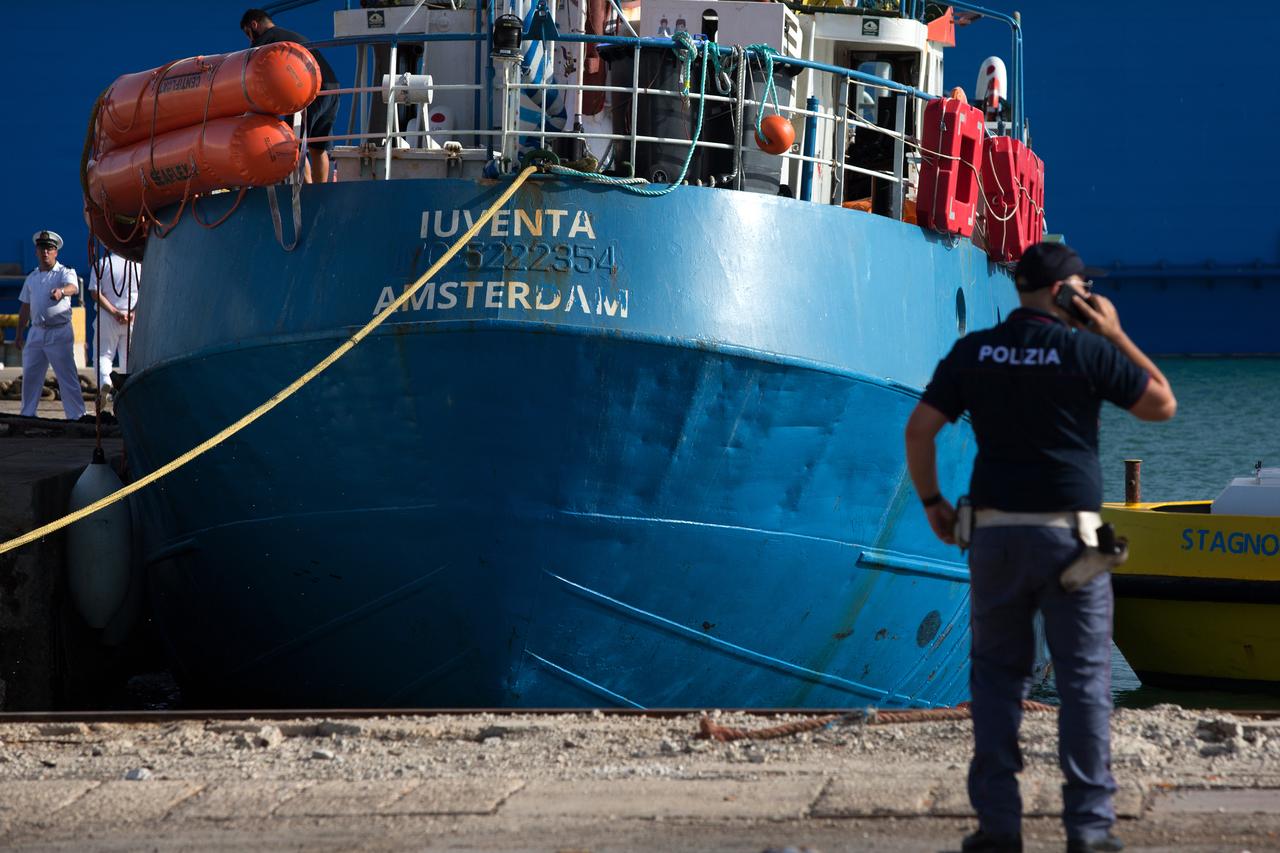 Schiff Iuventa von Sea Watch im Hafen, daneben steht ein Polizist