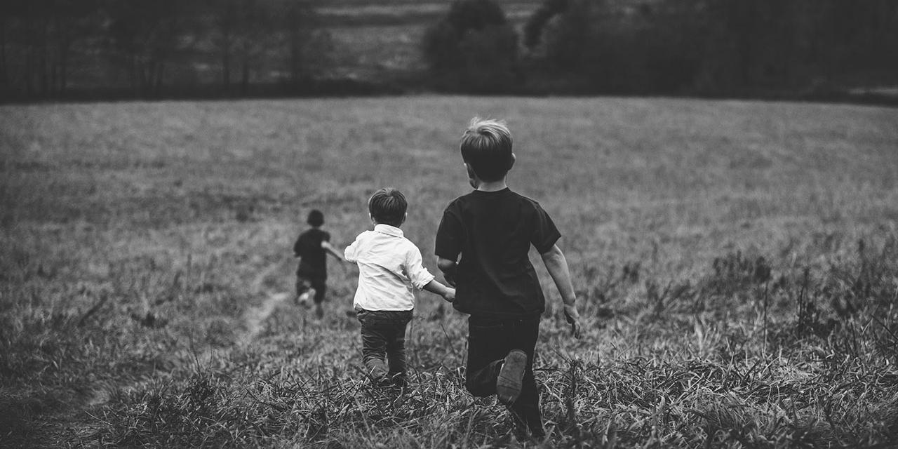 Drei Jungen laufen über eine Wiese
