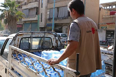 Caritas-Mitarbeiter auf einem Pickup mit Wasserflaschen