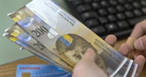 Person zählt ein Bündel Schweizer 200-Franken-Banknoten