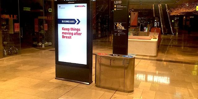 """Leuchtwerbung in nächtlichem Einkaufszentrum: """"Business: Get ready for Brexit"""""""