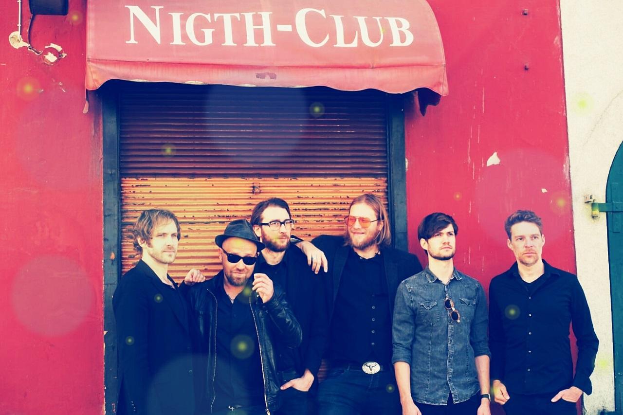 """Die Musiker von Rote Augen stehen im Grazer Bezirk Lend vor einem einstigen Bordell, auf das noch die Aufschrift """"Night Club"""" verweist."""