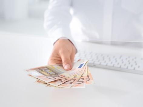 Hand mit 50 Euro-Scheinen (Bankangestellter hinter Glas)