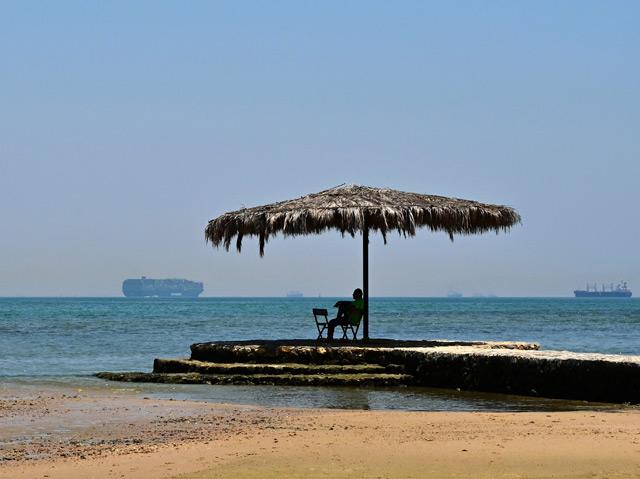 Blick auf den heutigen Suezkanal, im Vordergrund ein Mann unter einem Sonnenschirm