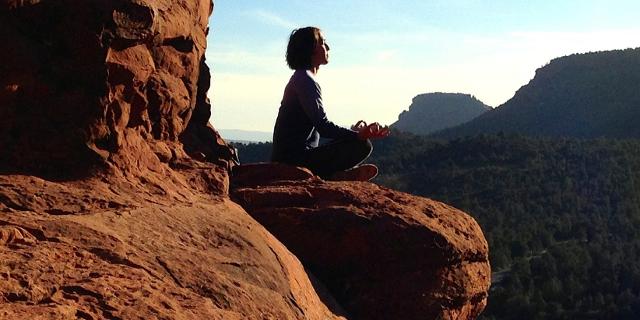 Eine Frau macht auf einem Felsen Yoga