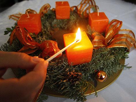 Ein Adventkranz, bei dem mit einem Zündholz die erste Kerze angezündet wird.