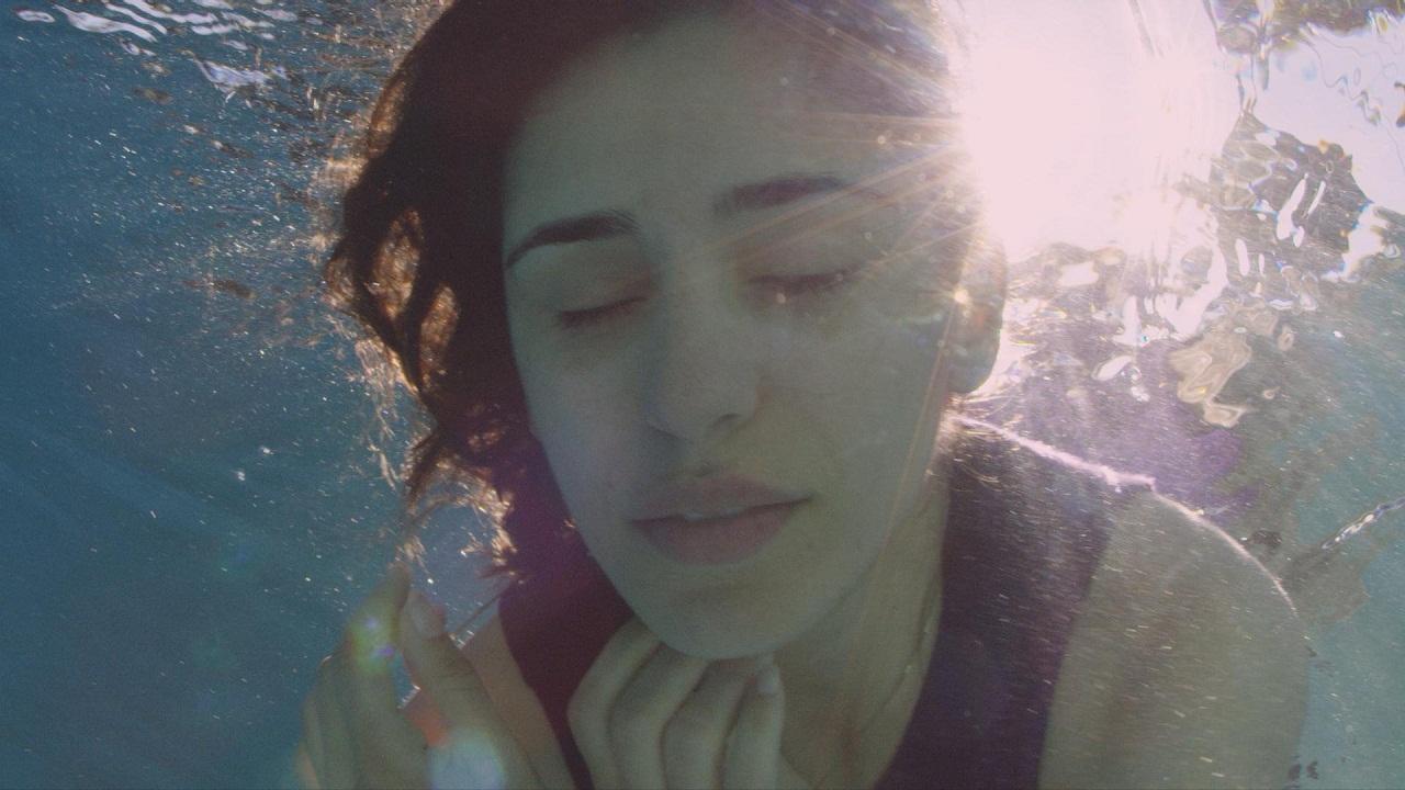 Maryam Zaree unter Wasser mit geschlossenen Augen.