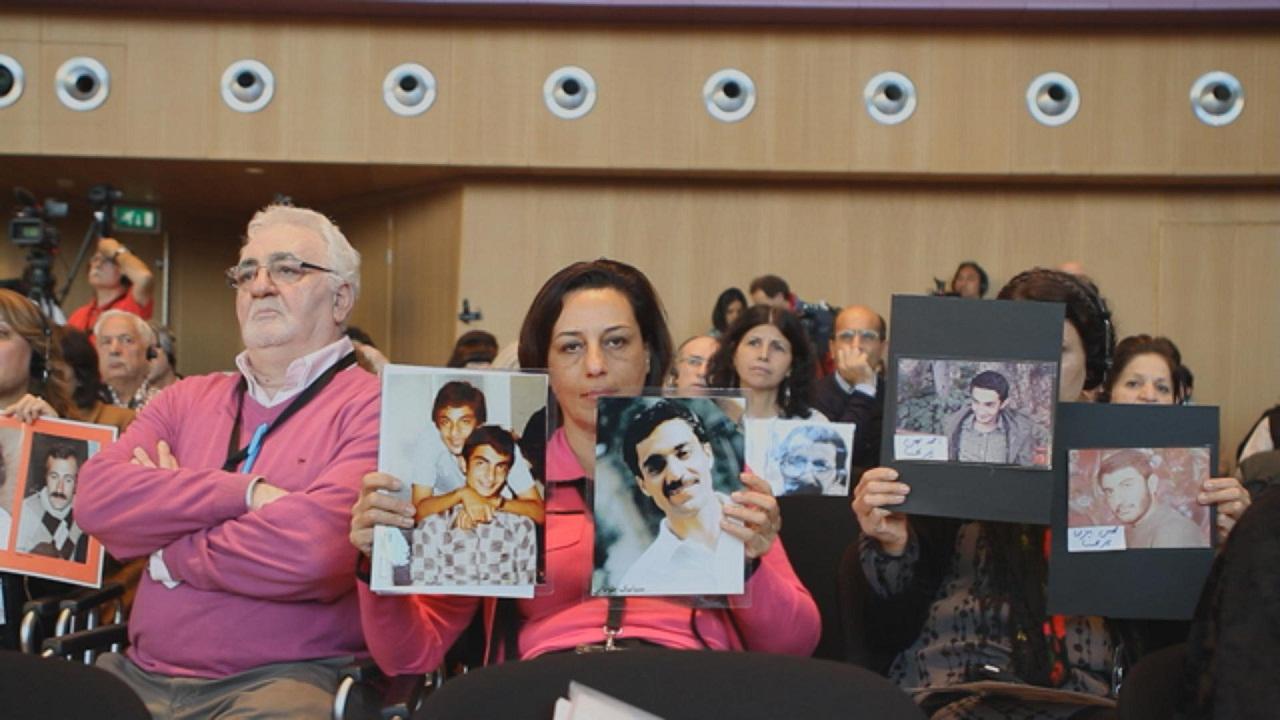"""Angehörige von Folteropfern halte deren Bilder hoch. Filmstill aus """"Born in Evin""""."""