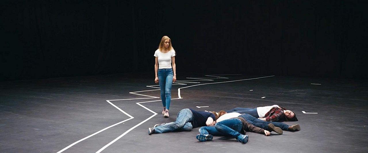Jugendliche bringen Klebebänder in einem Bühnenraum an.