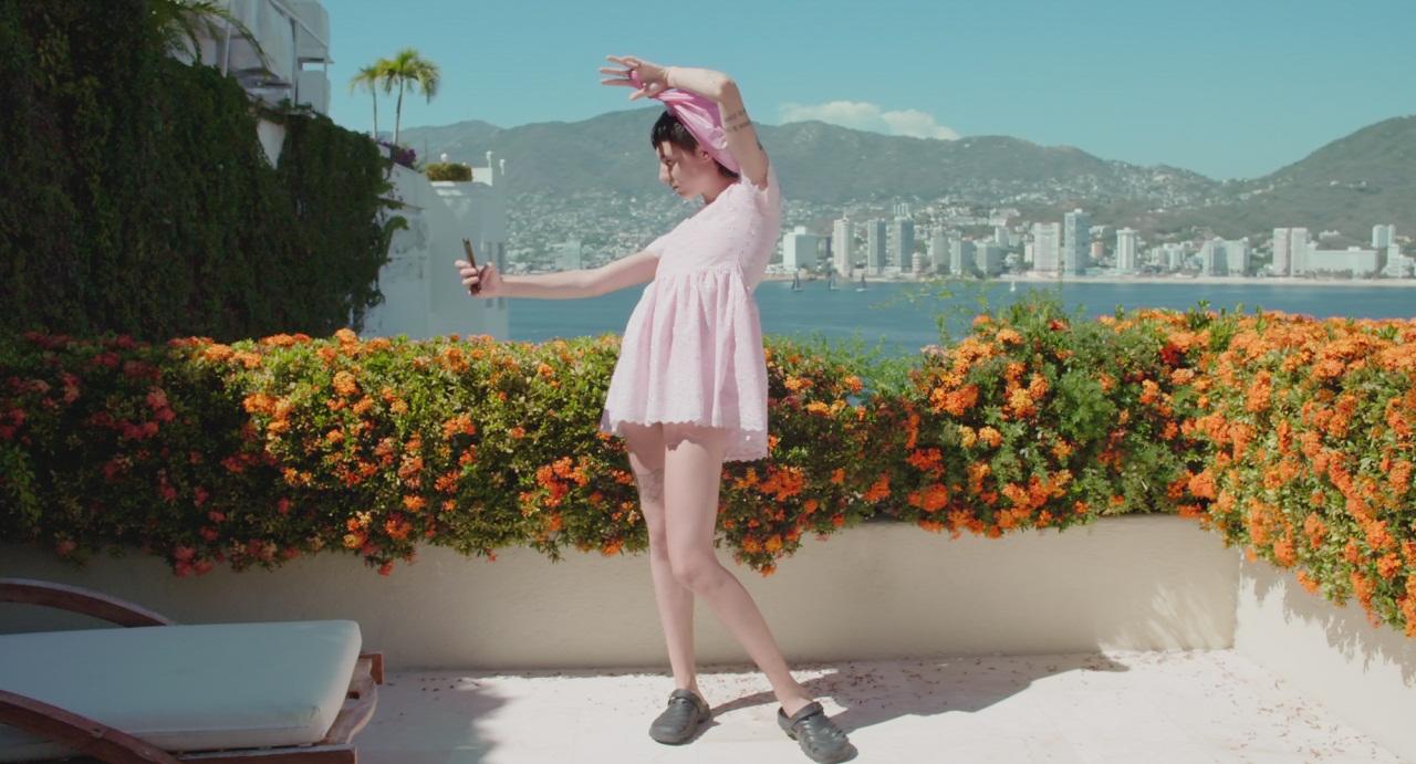 """Eva Collé steht auf einer Terrasse und fotografiert sich mit dem Smartphone. Filmstill aus """"Searching Eva""""."""
