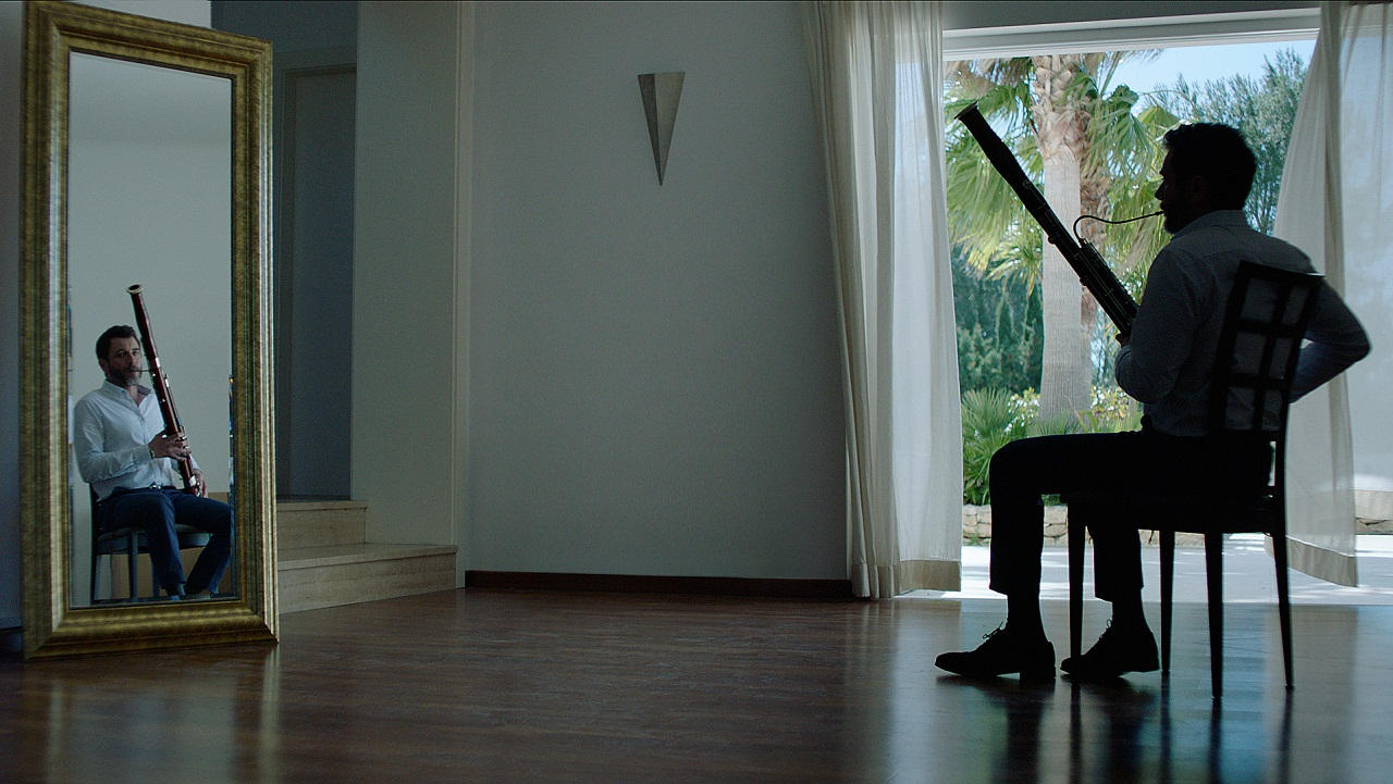 """Der Schauspieler Alex Brendemühl spielt einen Musiker, der beim Fagottspielen vor dem Spiegel sitzt. Filmstill aus """"Der Taucher""""."""