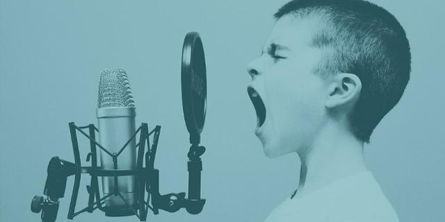 Junge singt in ein Mikrophon