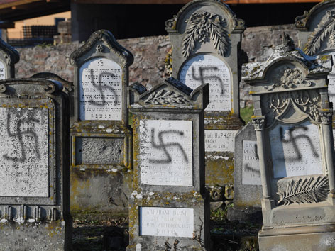 Mit Hakenkreuzen beschmierte Grabsteine auf einem jüdischen Friedhof im Elsass, Frankreich.