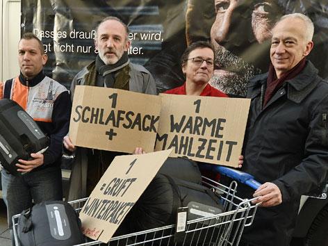 """Caritas-Präsident Michael landau, Schauspieler Kalr markovics und zwei HelferInnen mit einem """"Gruft""""-Winterpaket"""