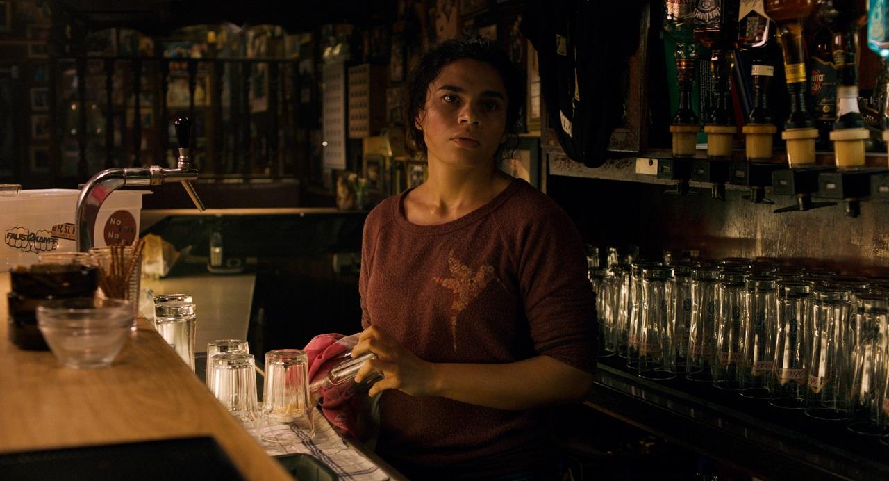 Alina Șerban hinter einer Bar, sie putzt Gläser