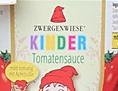 """Ein Mensch verkleidet als lebensgroßes Glas Kinder-Tomatensoße, ein Mann daneben hält den Negativpreis """"Goldener Windbeutel"""" in Händen, im Hintergrund die Firmenzentrale von Zwergenwiese"""