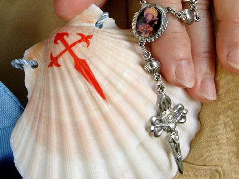 Eine Jakobsmuschel mit rotem Kreuz darauf als Zeichen des Pilgerns nach Santiago de Compostela.