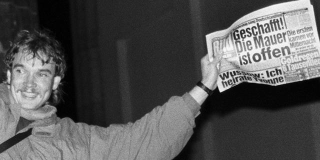 """Ein Mann hält sich am 9.11.1989 in Berlin an dem Schild mit der Aufschrift """"Platz vor dem Brandenburger Tor"""" fest und schwenkt eine BILD Zeitung mit dem Titel """"Geschafft! Die Mauer ist offen""""."""