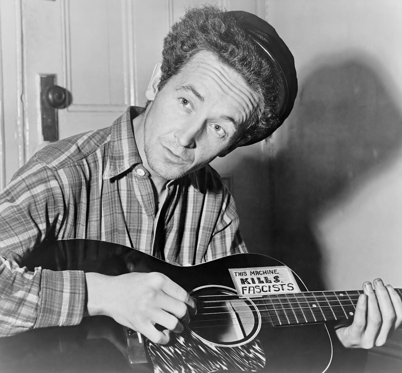 """Woodie Guthrie und seine Gitarre mit dem Sticker """"This machine kills fascists"""""""
