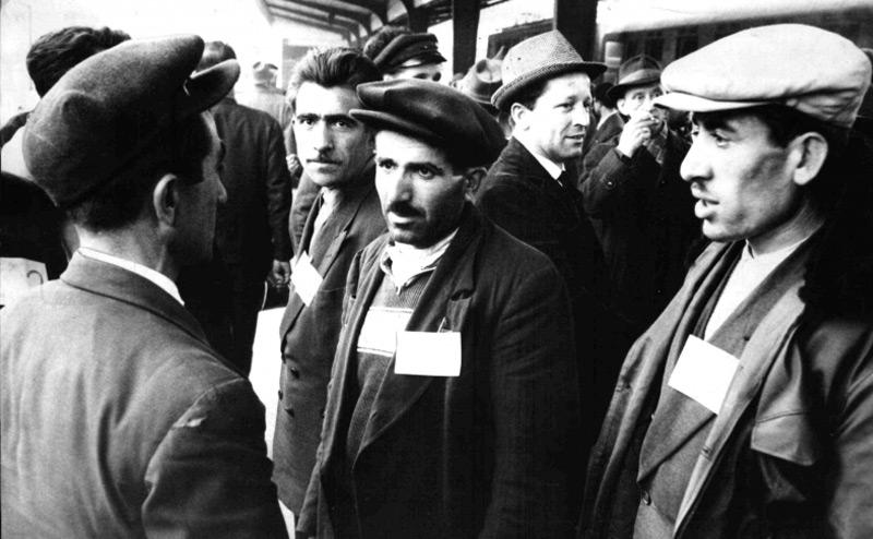 Türkische Gastarbeiter mit Namensschildern auf der Brust 1964 an einem Wiener Bahnhof