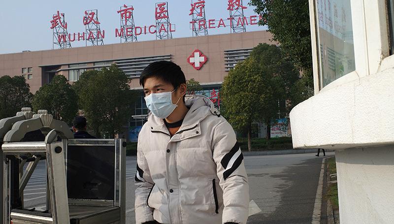 Mann mit Atemschutzmaske vor Krankenhaus