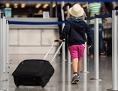 Ein Kind mit Strohhut zieht seinen Koffer am Flughafen Frankfurt