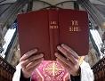 Ein Priester hält eine aufgeschlagene Bibel in den Händen