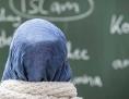 Eine Schülerin mit Kopftuch sitzt in einer Schule bei einer Unterrichtsstunde zum Thema Islam vor einer Tafel