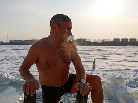 Ein Mann in Russland beim traditionellen Eisbad zu Epiphanias