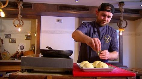 Koch streut Sesam auf die Burger Brötchen