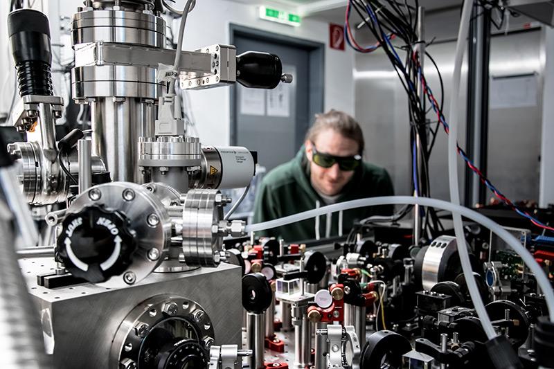 Forscher vor einem Experimentaltisch mit unzähligen Kabeln, Strahlenteilern und einer Vakuumkammer