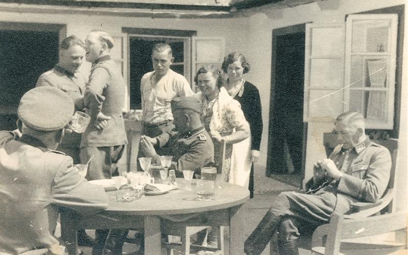 Niemann (3.v.l.) im Kreis einer Gruppe auf einer Terasse in Sobibor, auf dem Tisch sind teilweise hochwertige Kristallgläser erkennbar, die wahrscheinlich aus dem Besitz der Ermordeten stammten.