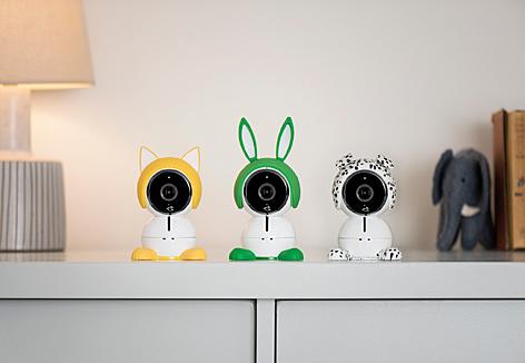 Drei Arlo Baby Webcams - eine mit Katzen-, eine mit Hasen- und eine mit Hundeohren - stehen nebeneinander auf einem weißen Regal