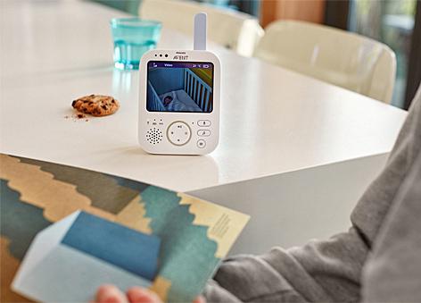 Ein Video-Babyphon steht auf einem Esstisch, daneben ein Keks und ein Glas Wasser. Im Vordergrund liest ein Elternteil in einer Zeitschrift