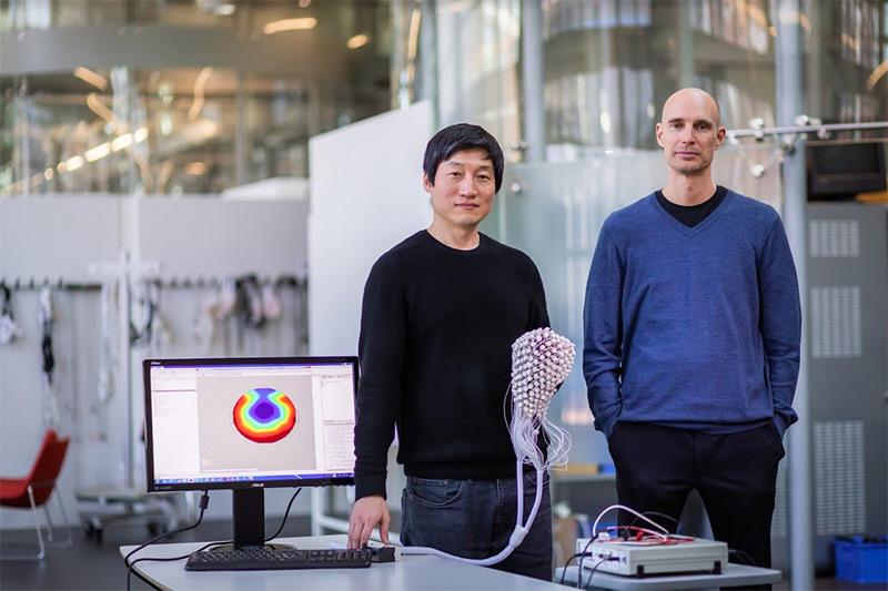 Forscher Olaf Blanke und Hyeongdong Park mit einer EEG-Haube