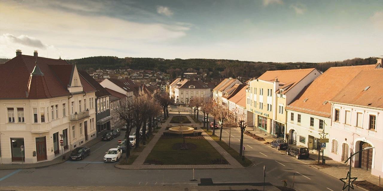 """Filmstill """"Der schönste Platz auf Erden"""" zeigt eine Stadtansicht von Pinkafeld im Burgenland, eine Straße und Häuser"""