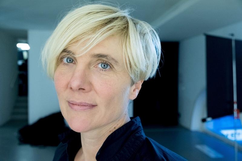 Die Filmemacherin und Cutterin Elke Groen trägt einen kurzen Haarschnitt und lächelt