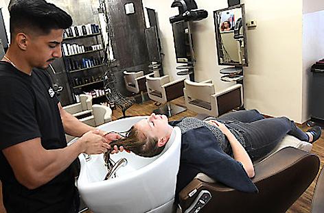 Ein Friseur wäscht die Haare einer Kundin