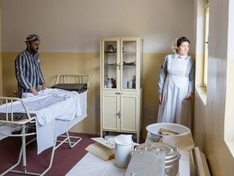 Maria Stromberger blickt aus dem Fenster der SS-Krankenstation. Ein Häftling hilft ihr bei der Arbeit