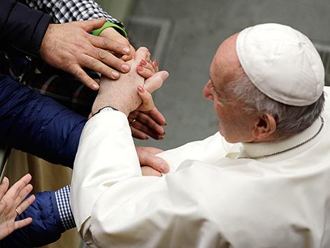 Papst Franziskus hält die Hände einiger Gläubiger