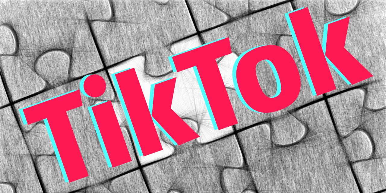 """Schriftzug """"TikTok"""" im Hintergrund schwarz-weiße Puzzlesteine"""