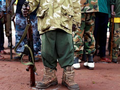 Ein Kindersoldat in zu großem Militärgewand