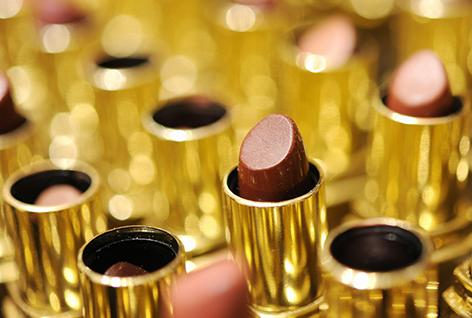 Verschiedene Lippenstifte in goldener Hülle in einem Parfumerie-Regal