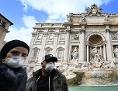 Touristen mit Atemschutzmasken vor dem Trevi-Brunnen in Rom