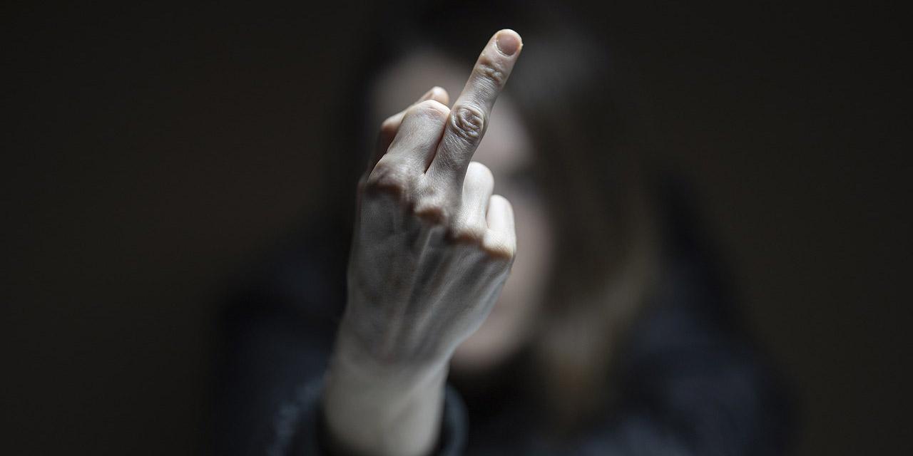 Frau streckt Mittelfinger vor
