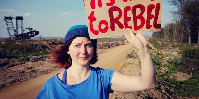 """Die """"Ende Gelände""""-Sprecherin Kathrin Henneberger steht auf einem Feld und hält ein Schild hoch mit der Aufschrift """"It's time to rebel"""""""