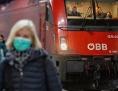 Eine Frau mit Atemschutzmaske geht vor einem Zug der ÖBB am Hauptbahnhof in München entlang