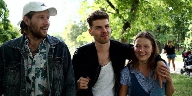 """Zwei Männer und eine Frau sind vergnügt im Freien unterwegs, sie sehen aus wie gute Freunde. Filmstill aus """"3freunde2feinde""""."""